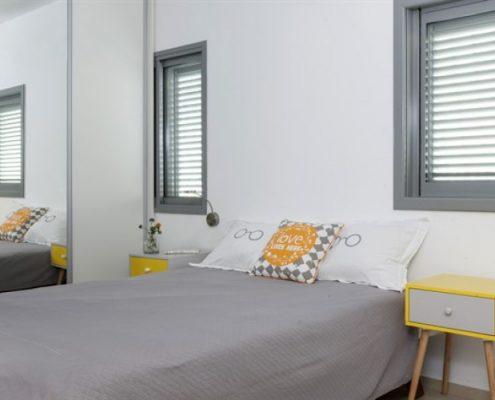 עיצט חדר הורים בגוונים של אפור צהוב