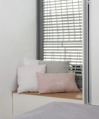 עיצוב חדר שינה בשילוב כריות על עדן החלון